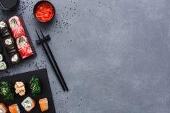 Комплект взгляд сверху maki и кренов суш на деревенской предпосылке серого цвета и сезама Стоковое Изображение