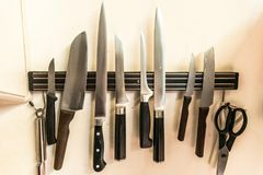 Комплект высококачественных инструментов ножей кашевара кухни на смертной казни через повешение доски магнита на стене Стоковое фото RF
