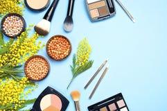 Комплект декоративных косметик для щеток корректора теней для век румян порошка состава и цветков мимозы на голубой предпосылке с стоковые фото