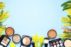Комплект декоративных косметик для щеток корректора теней для век румян порошка состава и цветков мимозы на голубой предпосылке с стоковые фотографии rf