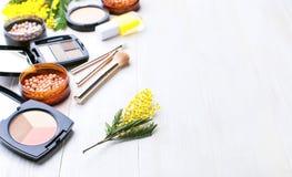 Комплект декоративных косметик для щеток корректора теней для век румян порошка состава и цветков мимозы на светлом деревянном ba стоковые фото