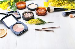 Комплект декоративных косметик для щеток корректора теней для век румян порошка состава и цветков мимозы на светлом деревянном ba стоковое изображение