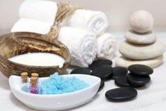 Комплект для обработок курорта с молоком кокоса, горячими камнями и голубой солью для принятия ванны расположен на белой мраморно Стоковое Фото