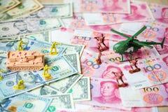Комплект игрушки, танк, солдаты и вертолет помещенные на банкнотах США, куча валюты доллара и банкноты фарфора Стоковая Фотография
