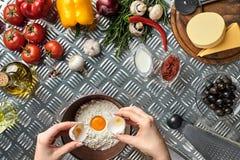 Комплект ингридиентов для руки ` s пиццы и хлебопека ломает яичка в шар на таблице металла Стоковые Изображения