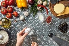 Комплект ингридиентов для руки ` s пиццы и хлебопека ломает яичка на таблице металла Стоковое Изображение RF