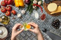 Комплект ингридиентов для руки ` s пиццы и хлебопека ломает яичка на таблице металла Стоковое Изображение