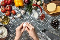 Комплект ингридиентов для руки ` s пиццы и хлебопека ломает яичка на таблице металла Стоковое фото RF