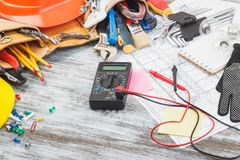 Комплект инструментов конструкции, чертежей и вольтамперомметра, деревянной предпосылки Стоковое Фото