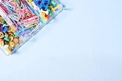 Комплект канцелярских принадлежностей сделанный из пестротканых кнопок и бумажных зажимов в коробке дальше Стоковые Изображения