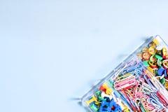 Комплект канцелярских принадлежностей сделанный из пестротканых кнопок и бумажных зажимов в коробке дальше Стоковые Фотографии RF