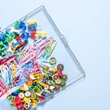 Комплект канцелярских принадлежностей сделанный из пестротканых кнопок и бумажных зажимов в коробке дальше Стоковое Фото