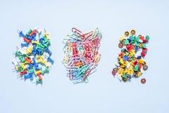 Комплект канцелярских принадлежностей сделанный из пестротканых кнопок и бумажных зажимов в различных кучах Стоковое Изображение RF