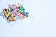 Комплект канцелярских принадлежностей сделанный из пестротканых кнопок и бумажных зажимов в коробке дальше Стоковая Фотография