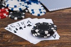 Комплект карточек от черных костюмов в покере на предпосылке старой таблицы Стоковое Фото
