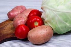 Комплект картошек капусты овощей на предпосылке деревянного стола Стоковые Изображения RF