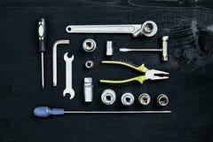 Комплект ключа инструментов гаечного ключа и отвертки гнезда плоскогубцев на черной деревянной предпосылке Стоковая Фотография