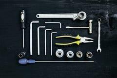 Комплект ключа инструментов гаечного ключа и отвертки гнезда плоскогубцев на черной деревянной предпосылке Стоковая Фотография RF