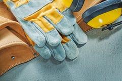 Комплект кожаных earmuffs защитных перчаток пояса инструмента на бетоне Стоковая Фотография