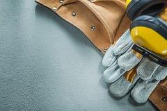 Комплект кожаных earmuffs перчаток безопасности пояса инструмента на задней части бетона Стоковые Изображения