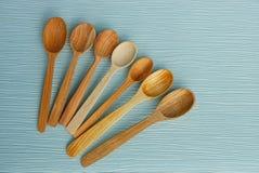 Комплект коричневых деревянных ложек на голубой таблице Стоковые Фотографии RF