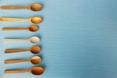 Комплект коричневых деревянных ложек на голубой таблице Стоковое Фото