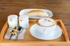 Комплект кофе, капучино в белой кофейной чашке и хлеба на древесине Стоковые Изображения RF
