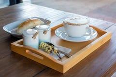 комплект кофе, капучино в белой кофейной чашке с хлебом дальше сватает Стоковые Фотографии RF