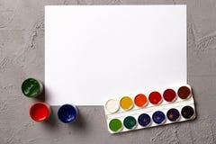 Комплект красок акварели, для красить и пустой листа белой бумаги sketchbook на предпосылке текстуры конкретной поверхности Стоковая Фотография RF