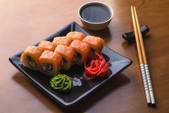 Комплект крена суш Филадельфии установил на керамическую плиту с wasabi, имбирем, соевым соусом стоковое фото