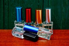 Комплект малых покрашенных бутылок с дух на таблице около деревянной стены Стоковое фото RF