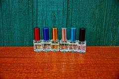 Комплект малых покрашенных бутылок с дух на таблице около деревянной стены Стоковые Фото