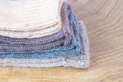 Комплект милого малого различного покрашенного кашемира связал newborn носки младенца на деревянной предпосылке стола Стоковое фото RF