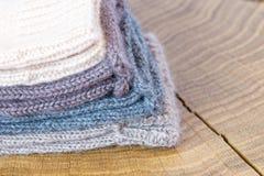 Комплект милого малого различного покрашенного кашемира связал newborn носки младенца на деревянной предпосылке стола Стоковые Изображения RF