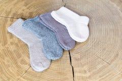 Комплект милого малого различного покрашенного кашемира связал newborn носки младенца на деревянной предпосылке стола Стоковое Изображение