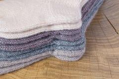 Комплект милого малого различного покрашенного кашемира связал newborn носки младенца на деревянной предпосылке стола Стоковые Фото