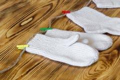 Комплект милых связанных носок и шпицрутенов младенца кашемира newborn повиснул на штырях против деревянной предпосылки Стоковые Фото