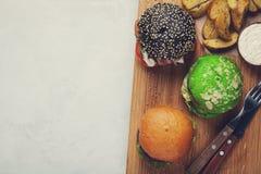 Комплект мини домодельного бургера 3 с мраморными говядиной и овощами на деревянной доске концепция высококалорийной вредной пищи Стоковое Изображение RF