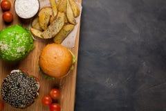 Комплект мини домодельного бургера 3 с мраморными говядиной и овощами на деревянной доске концепция высококалорийной вредной пищи Стоковые Изображения