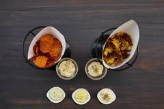 Комплект много закусок для вина или пива: 2 вида домашних картофельных стружек и 5 различных соусов на коричневом деревянном стол Стоковое Изображение
