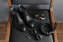 Комплект мужских одежд и аксессуаров Groom собирает в утре Набор на черном стуле женщина типа пер дела белая стоковые фотографии rf