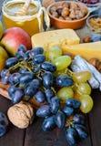 Комплект осени продуктов: виноградины, грецкие орехи, фундуки, сливы, мед, сыр, изюминки, груши Стоковая Фотография RF