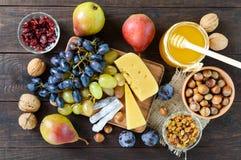 Комплект осени продуктов: виноградины, грецкие орехи, фундуки, сливы, мед, сыр, изюминки, груши, высушили клюквы на деревянной пр Стоковые Изображения RF