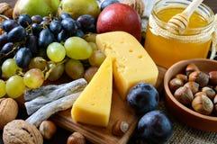 Комплект осени продуктов: виноградины, грецкие орехи, фундуки, сливы, мед, сыр, изюминки, груши, высушили клюквы на деревянной пр Стоковое Изображение RF