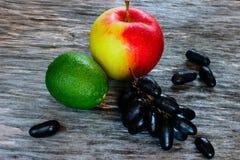 Комплект плодоовощ свежие известка, яблоко и виноградины на деревянной поверхности Стоковое Фото
