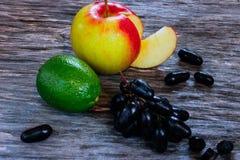 Комплект плодоовощ свежие известка, яблоко и виноградины на деревянной поверхности Стоковое Изображение
