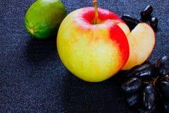 Комплект плодоовощ свежие известка, яблоко и виноградины на черной поверхности Стоковое Фото