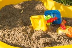 Комплект покрашенной пластмассы забавляется на песке, ящике с песком ` s детей в дне лета солнечном Стоковое Изображение