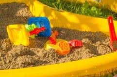 Комплект покрашенной пластмассы забавляется на песке, ящике с песком ` s детей в дне лета солнечном Стоковая Фотография RF