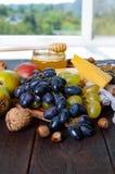 Комплект продуктов: виноградины, гайки, мед, груши, сыр на темном деревянном столе Стоковое Изображение RF